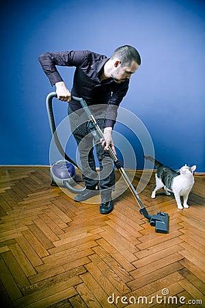 Man vacuuming, looking at cat