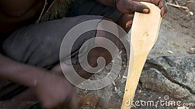 Man van een Afrikaanse stam snijdt mes af van een staaf houten instrument of gereedschap stock videobeelden
