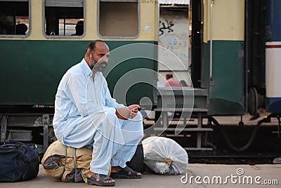 Man waits at station, trains delayed. Editorial Stock Photo