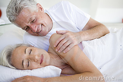 Man waking woman lying in bed sleeping