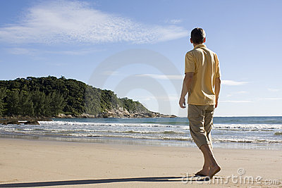 Man walking barefoot on a tropical beach
