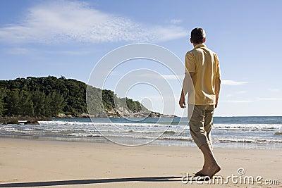 Man walking barefoot on a tropical beach