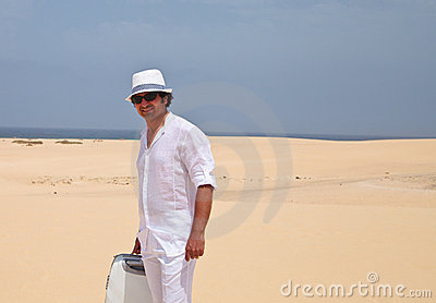 Man walking on a beach with luggage