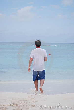 Man walking into the blue ocean