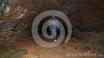 A man walking in a cave.