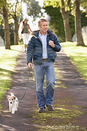 Man Walking Dog In Autumn Park