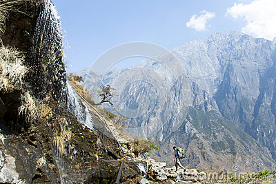 Man Walking by Mountainside Waterfall