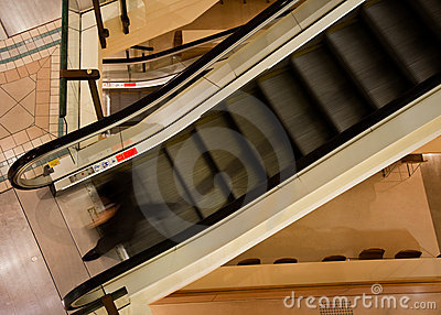 Man walking off descending escalator