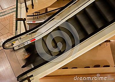 Man walking off descending escalator