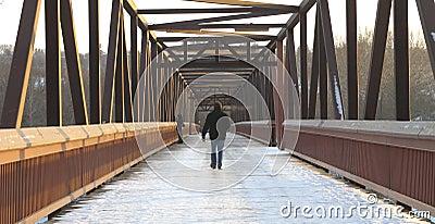 Man walking over footbridge