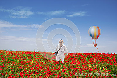 Man is Walking Through Red Poppy Field