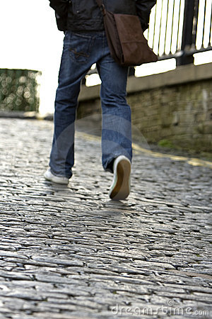 Man walking up a cobblestone road