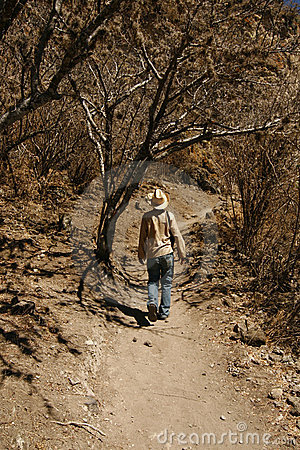 A man walking up the hillside in Mexican desert