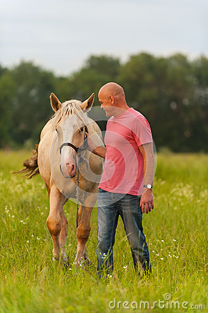 A man walks with his horse