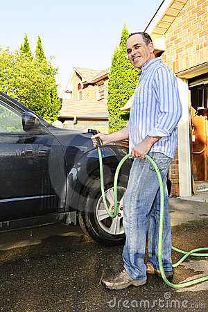 Man washing car on driveway