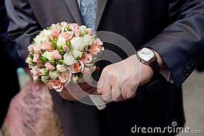 Man with watch hands a flower bouquet