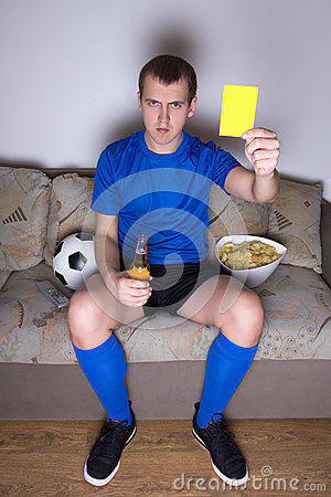 Man watching football on tv and showing yellow car