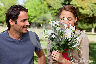 Man watching his friend smell a bunch of flowers