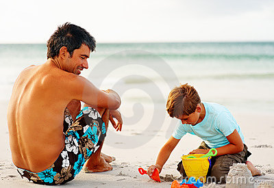 Man watching his son making a sand castle