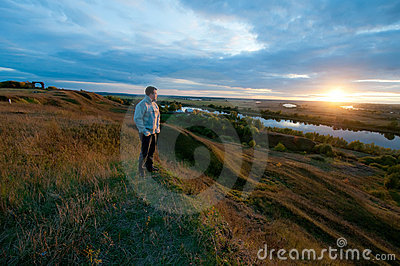 Man watching the sunset on the river