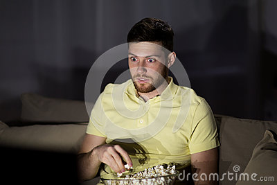 Man watching tv and eating popcorn at night Stock Photo