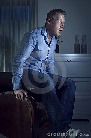 Man watching TV jumps up