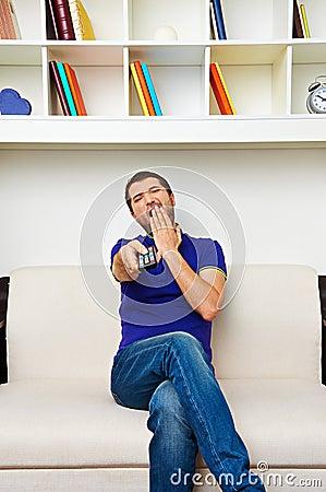 Man watching tv and yawning