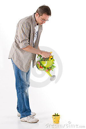 Man watering a small plant