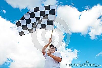 Man waving a checkered flag on a raceway