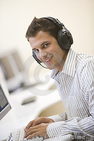 Man wearing headphones in computer room typing