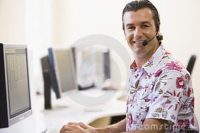 Man wearing headset in computer room smiling