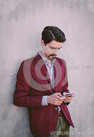 Man Wearing Maroon Blazer Leaning On Gray Concrete Wall While Using His Smartphone Free Public Domain Cc0 Image