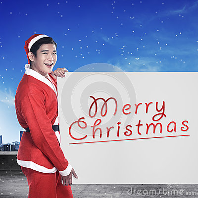 Free Man Wearing Santa Claus Costume Holding Banner With Merry Christmas Writing Stock Photo - 61626190