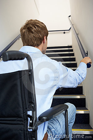 Man in wheelchair looking up at stairs