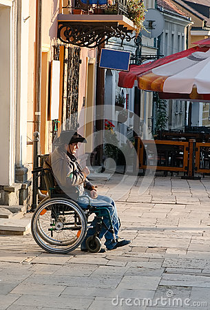 A man in a wheelchair on a walk Editorial Photo