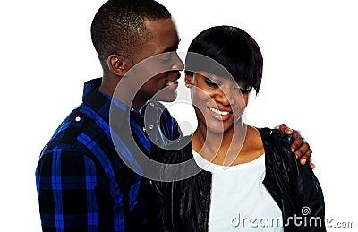 Man whispering in girlfriends ear