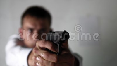 Man in a white shirt quickly pulls out a gun and takes aim. Theme of criminal with use of weapons and police in plain clothes. A professional works with a stock video footage
