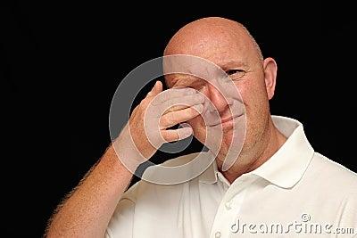 Man wiping tear from eye
