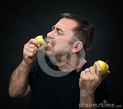 Free Man With An Appetite Eating A Green Apple Royalty Free Stock Image - 31441476