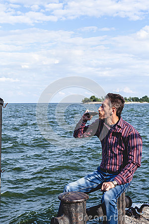 Free Man With Beard Is Drinking From Flask On River Quay Stock Photos - 97572483