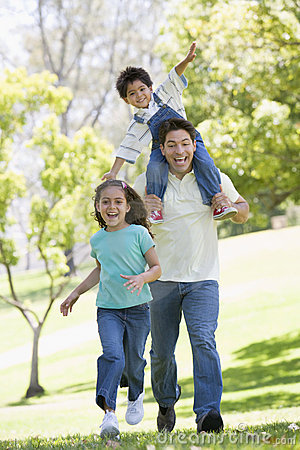 Free Man With Two Young Children Running Smiling Stock Images - 5771044
