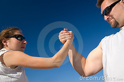 Man and Woman Arm Wrestling Outdoors