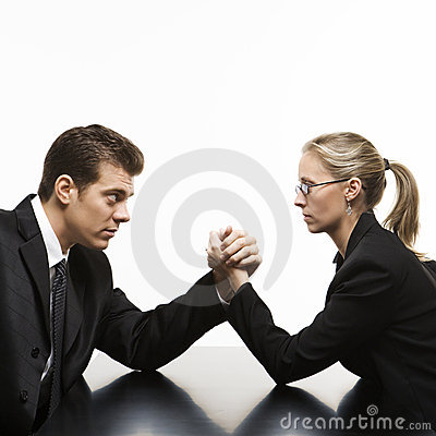 Man and woman arm wrestling on table.