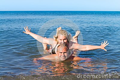 Man and woman of average years play sea as children