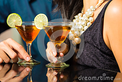 Man and woman at bar with cocktails