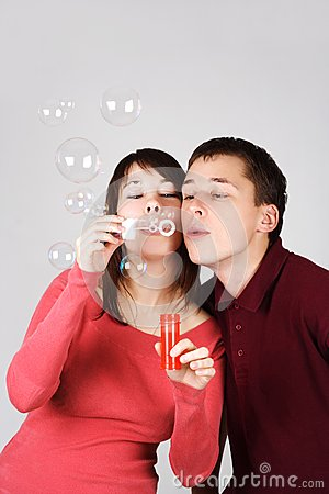 Man and woman blowing out soap bubbles