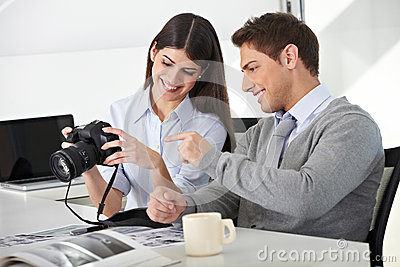 Man and woman with camera in office