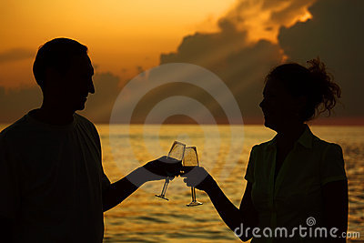 Man and woman clink glasses. Silhouettes on sea
