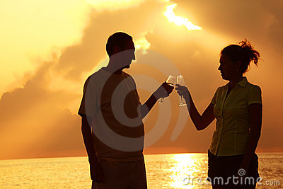 Man and woman clink glasses. Summer evening.