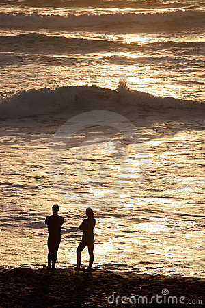 Man & woman couple on beach at sun set